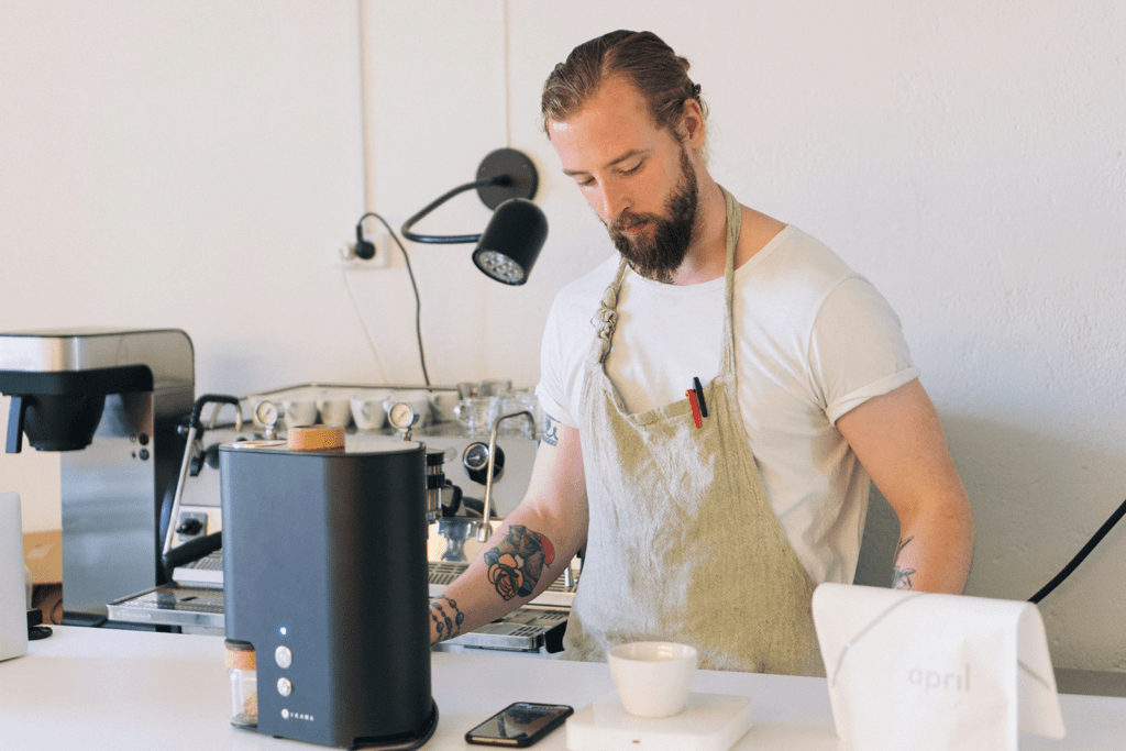 Patrik Rolf standing at bench roasting with IKAWA PRO V3 at April Coffee Roasters headquarters.